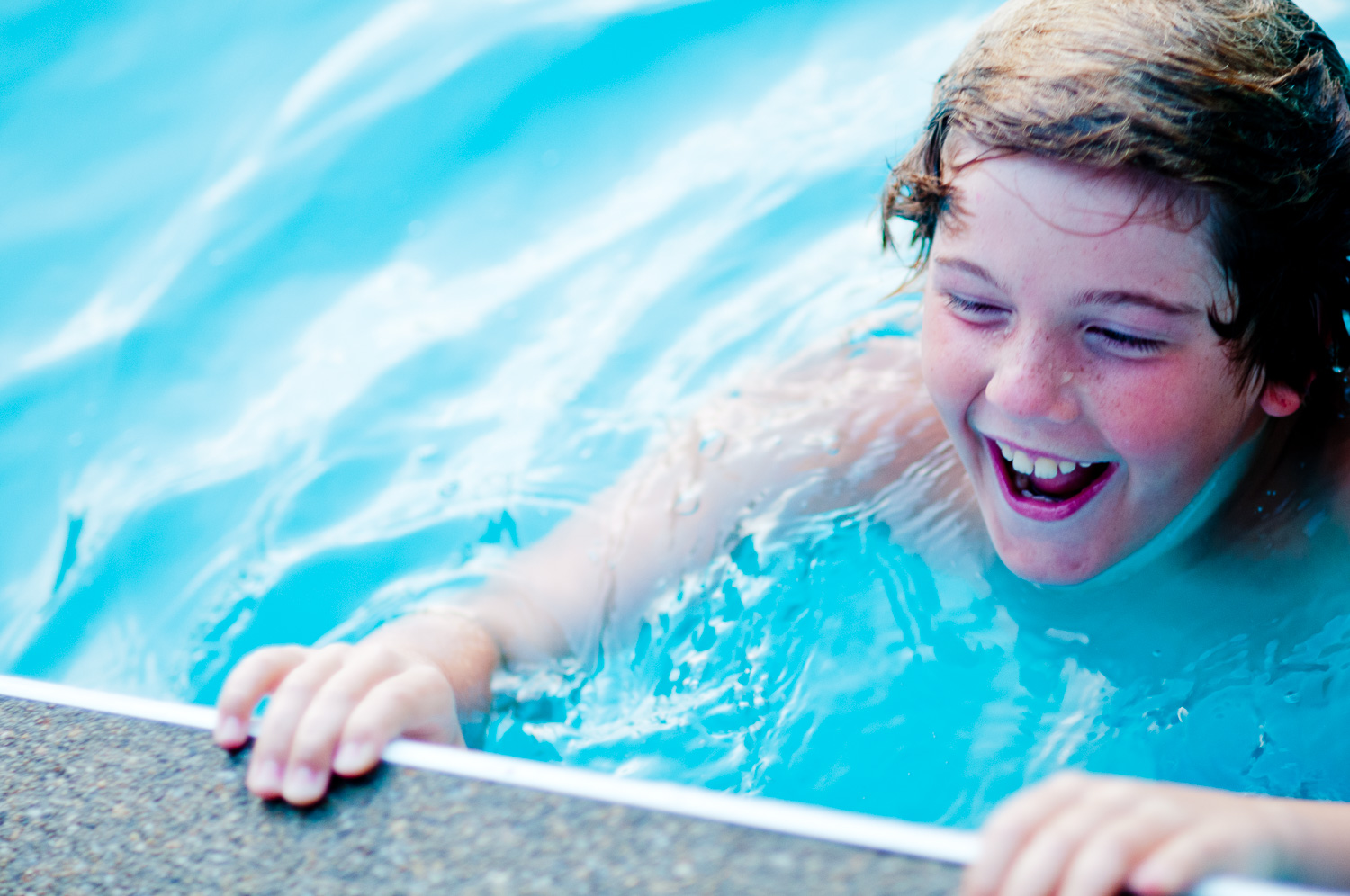 portrait of child smiling in pool