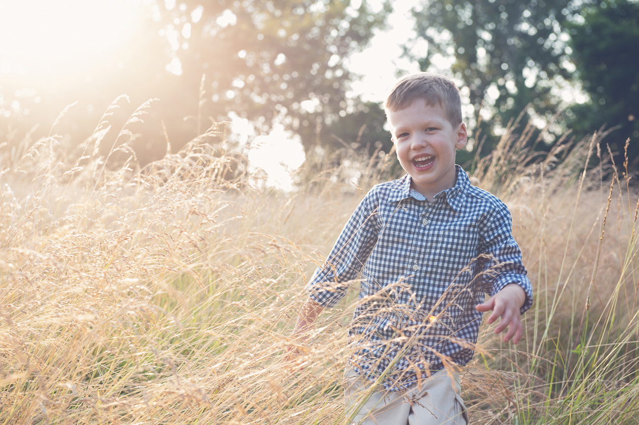 child running through tall grass at sunset